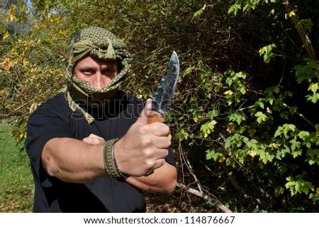 masked terrorist threatening with a knife - stock photo