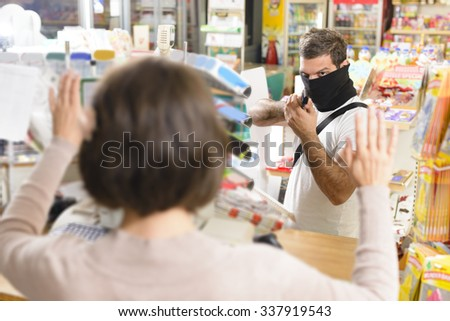Masked thief pointing a gun to sales woman in a store - stock photo