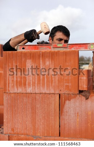 Mason adjusting brick wall - stock photo