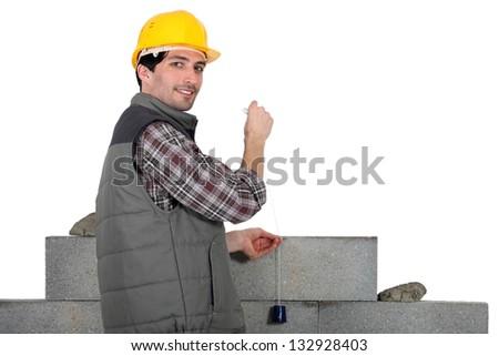 mason building a wall - stock photo