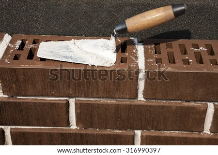 Mason's trowel on brown clinker brick. Insulation - foamglass. Masonry concept.  - stock photo