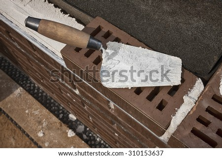 Mason's trowel on brown clinker brick. Masonry concept. - stock photo