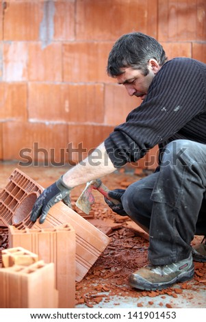 Mason smashing brick - stock photo