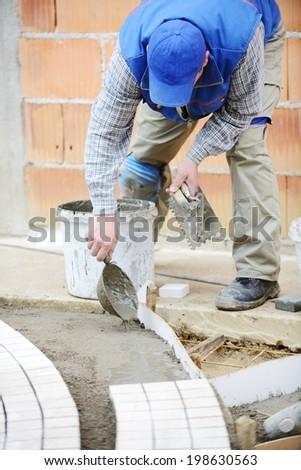 Mason worker making sidewalk pavement with stone blocks - stock photo