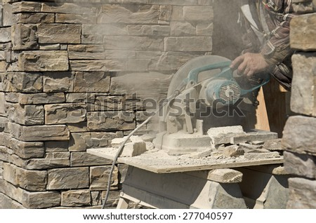 Masonry contractor using a dry circular tile or rock cutting saw to trim rock siding for a home installation - stock photo