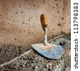 Masonry trowel above a rough unfinished concrete wall - stock photo