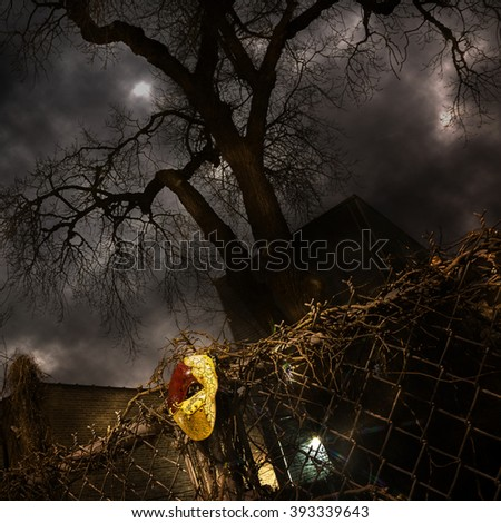 Masquerade - Venetian Mask on Fence with Dramatic Tree and Sky - stock photo