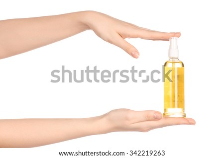 Massage and body care topic: a woman's hand holding a bottle of oil to the spa isolated on white background in studio - stock photo