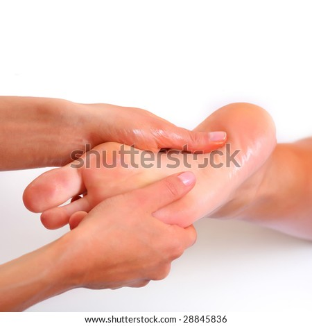 Massage and leaving of the female feet bared by a foot, isolated on a white background, please see some of my other parts of a body images: - stock photo