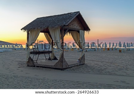 Massage canopy on a sandy beach in the early morning. Shallow depth of field. Focus on foreground. - stock photo