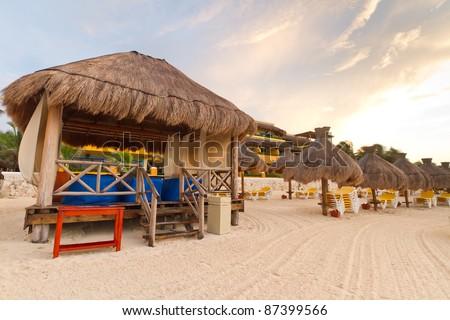 Massage hut on Caribbean beach at sunrise - stock photo