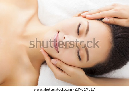 massage of face for woman in spa salon - stock photo