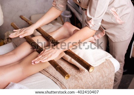 Massage of human foot in spa salon  with bamboo sticks. Closeup of legs - stock photo