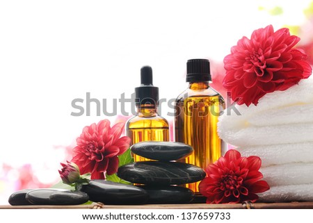 Massage oil,towel and red dahlia flower,isolated on white. - stock photo