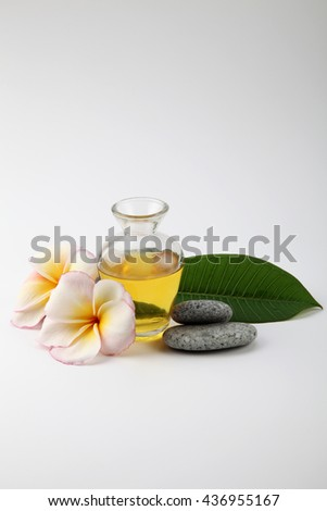 massage oil with frangipani and towel - stock photo