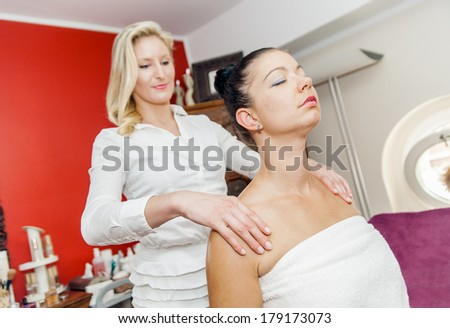 Massage procedure in a spa studio with two young woman - stock photo