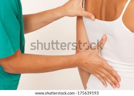 Massage therapist giving a back massage - stock photo