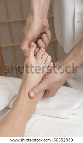 Massager's hands working with a woman's foot. Practice of reflexotherapy. - stock photo