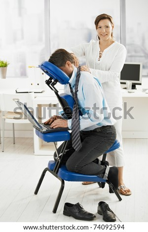 Masseur doing back massage in office, looking at camera, smiling. - stock photo