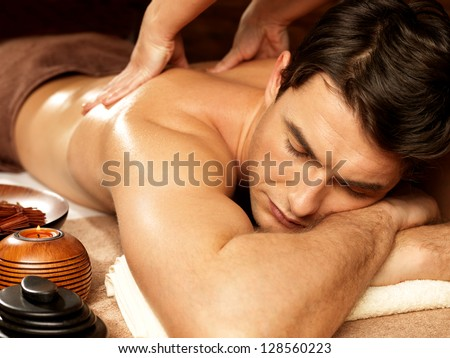 Masseur doing back massage on man body in the spa salon. Beauty treatment concept. - stock photo