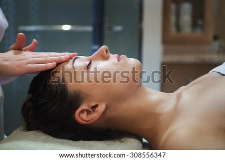 Masseur doing facial massage of an adult woman in the spa salon - stock photo