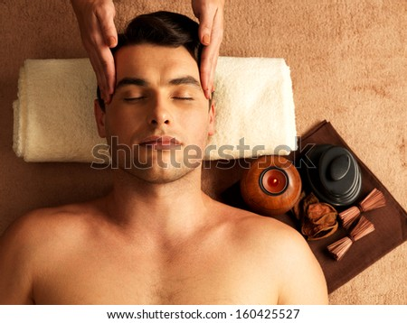 Masseur doing head massage of temples on man in the spa salon.  - stock photo