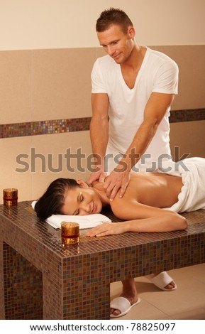 Masseur doing massage for client on massage table, relaxing treatment.? - stock photo