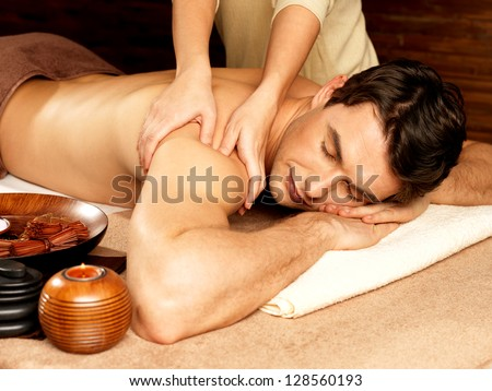 Masseur doing massage on man body in the spa salon. Beauty treatment concept. - stock photo