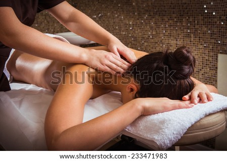 Masseur doing massage on woman body in the spa salon. - stock photo