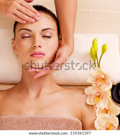 Masseur doing massage the head of an adult woman in the spa salon - stock photo