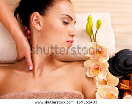 Masseur doing massage the neck of an adult woman in the spa salon - stock photo