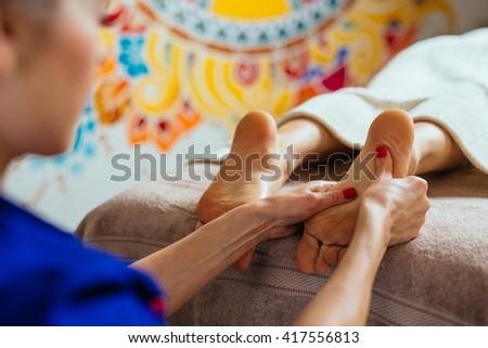 masseur doing reflexology, foot massage in exotic spa - stock photo