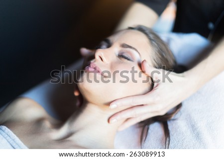 Masseur treating face of a beautiful, young woman lying on the massage table - stock photo