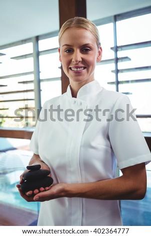 Masseuse holding stones massage at spa - stock photo