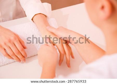 Masseuse massaging hand - stock photo