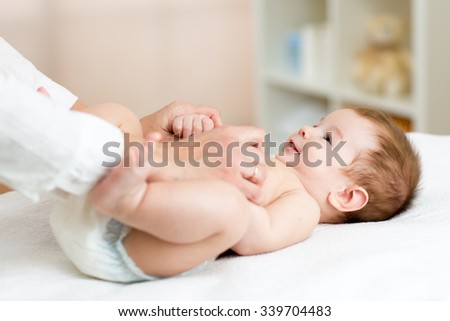 Masseuse or doctor massaging little baby boy - stock photo