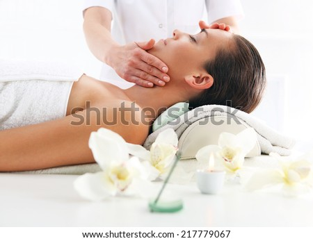 Masseuse - woman at face massage .Masseuse - woman at face massage .Attractive brunette woman in spa salon  - stock photo