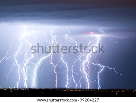 Massive colorful cloud to ground lightning bolts hitting the horizon of city lights. - stock photo
