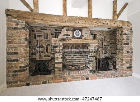 massive fireplace with exposed brick works and hard wood beams - stock photo