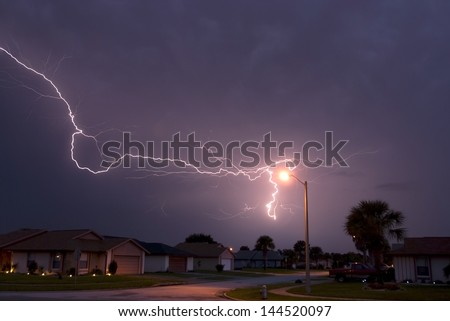 Massive lightning strike very close to homes in a neighborhood - stock photo