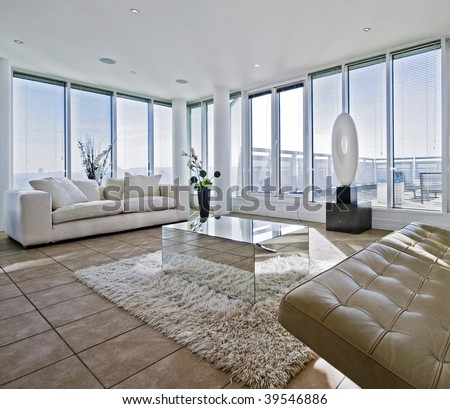massive luxury living room with chunky white fabric sofas and floor to ceiling windows - stock photo