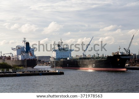 Massive tankers in an urban industrial port - stock photo