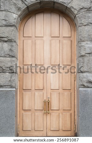 Massive wooden double door with stone arch - stock photo