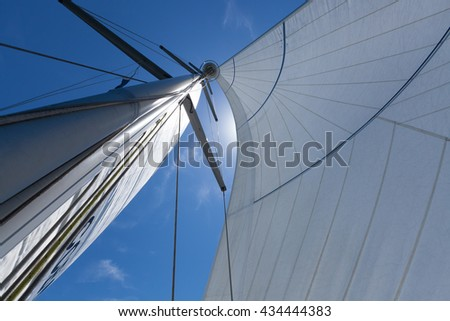 Mast and sails, close up shot from the deck looking up. Yacht sailing on a beautiful blue sunny day. - stock photo