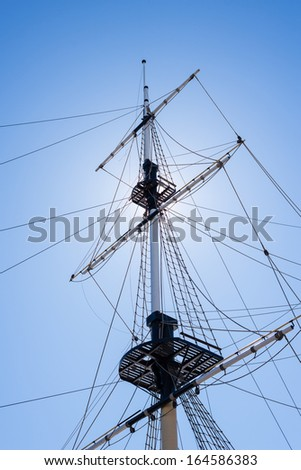 Mast of the sail boat on the blue sky background with sunlight - stock photo