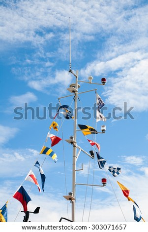 Mast with nautical signal flags against blue sky - stock photo