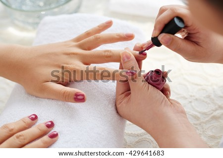 Master applying polish on fingernails on woman - stock photo