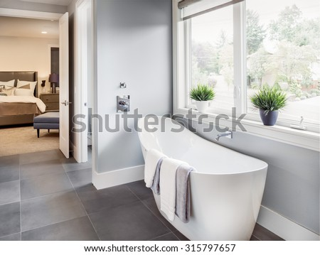 master bathroom interior in new luxury home: bathtub with view of master bedroom. includes tile floor, bathtub, faucet, window, and bed and stand in master bedroom - stock photo