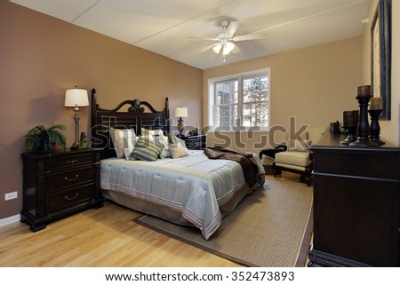 Master bedroom in condominium with dark wood furniture - stock photo