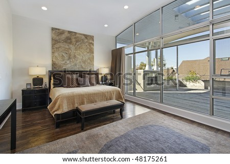 Master bedroom in luxury home with large deck - stock photo